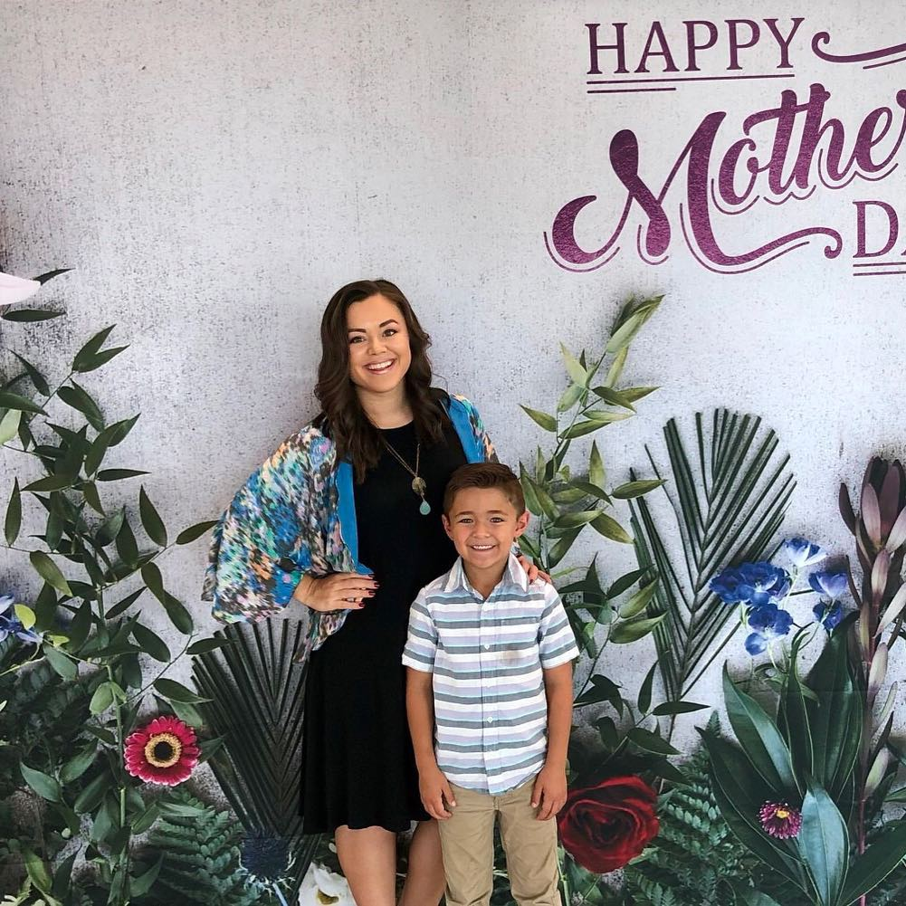 Shannon and son smiling and posing in front of flower mural