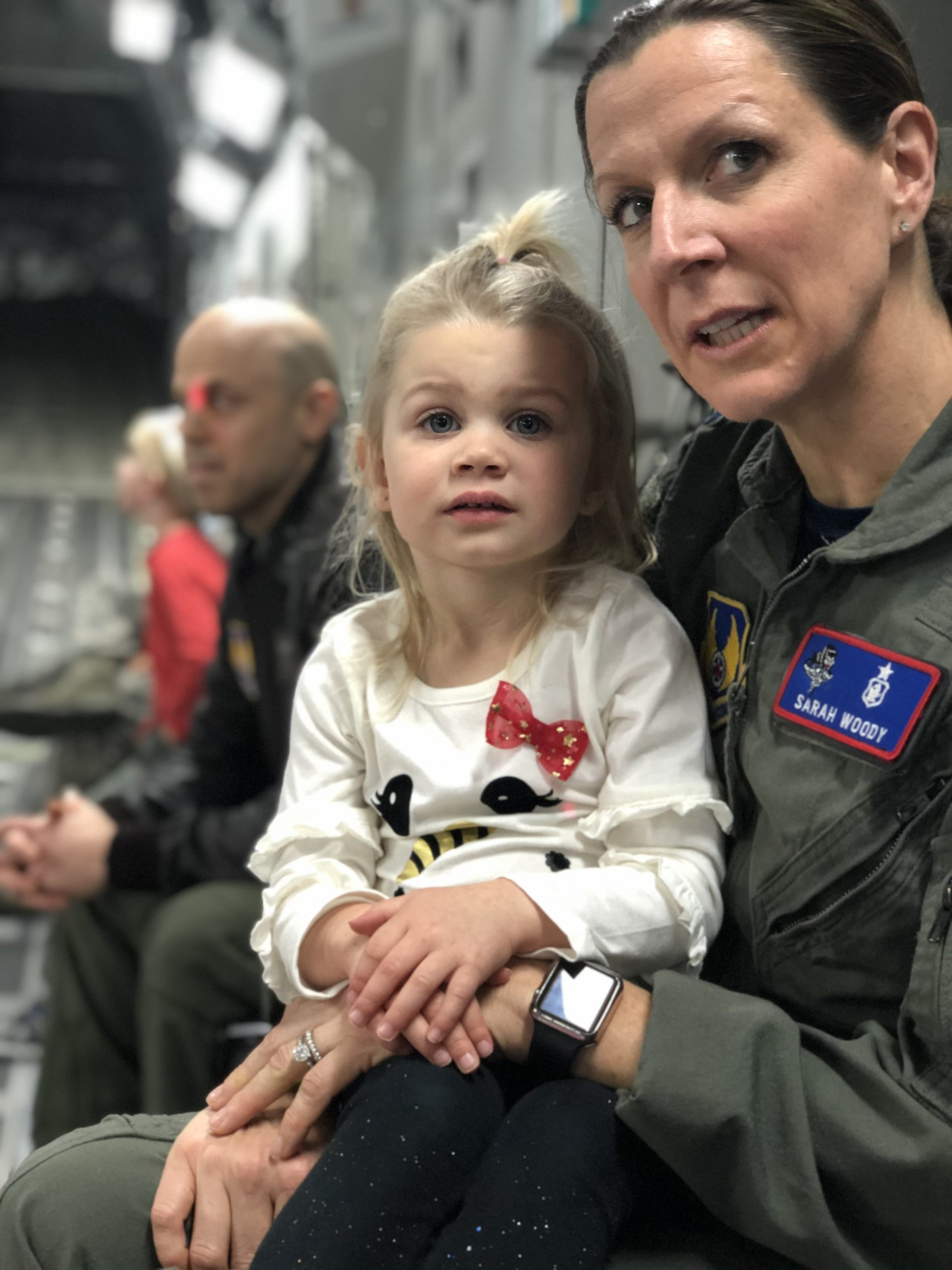 Sarah Woody in military uniform with a young child on her lap