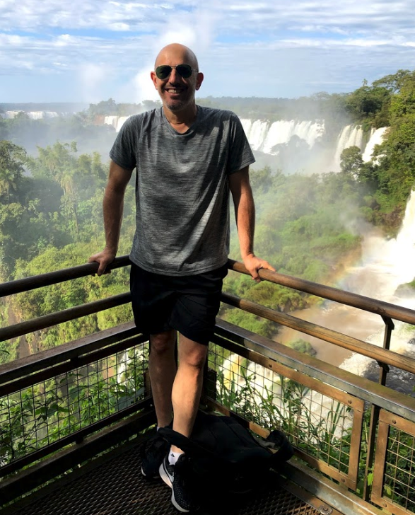 Rob Axelrod standing on a platform above a river smiling