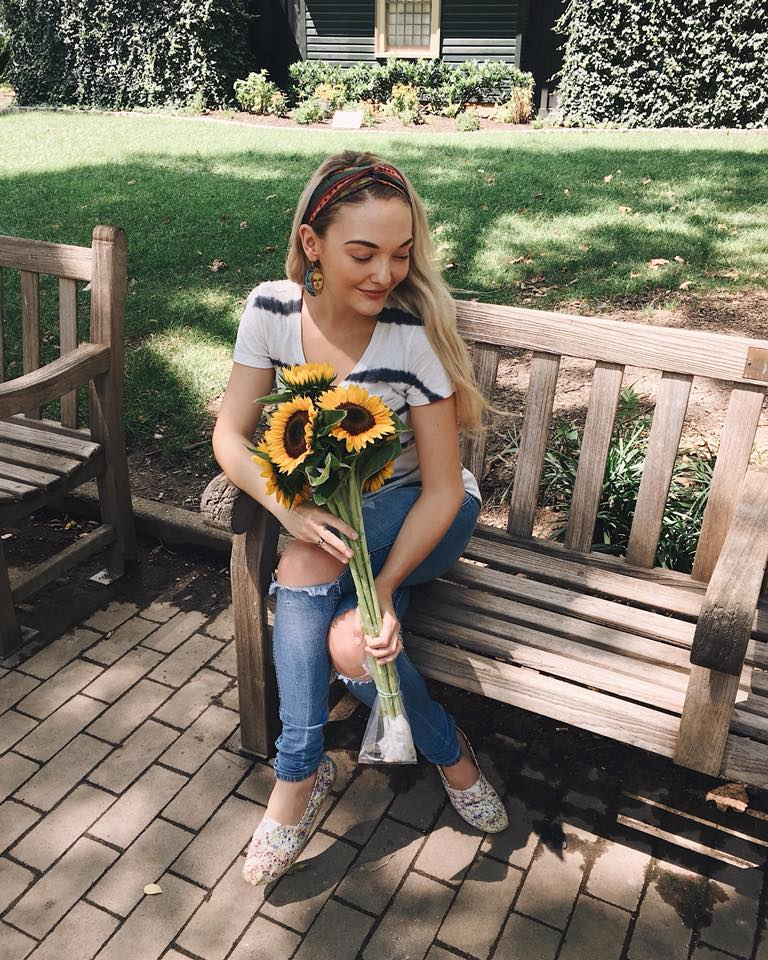 Miranda M. sitting on a bench holding a bouquet of sunflowers