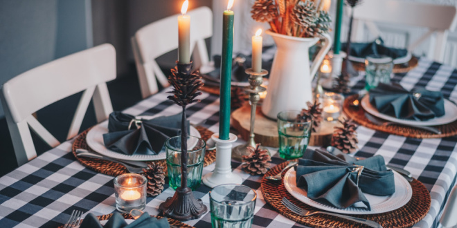 A kitchen table with a blue checkered table cloth with blue candles, and five place settings