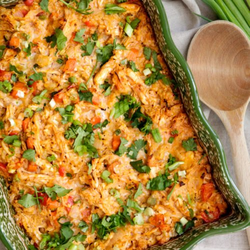 buffalo chicken casserole in a green dish with a wooden spoon next to the dish