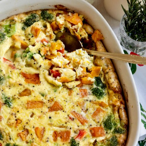 A casserole with sweet potatoes, broccoli, and red peppers in a white dish with a golden spoon taking a scoop out of the casserole