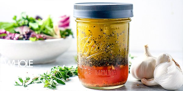 A jar of Whole30 easy Italian dressing sids next to a sprig of fresh thyme, a knot of garlic, and a fresh, green salad