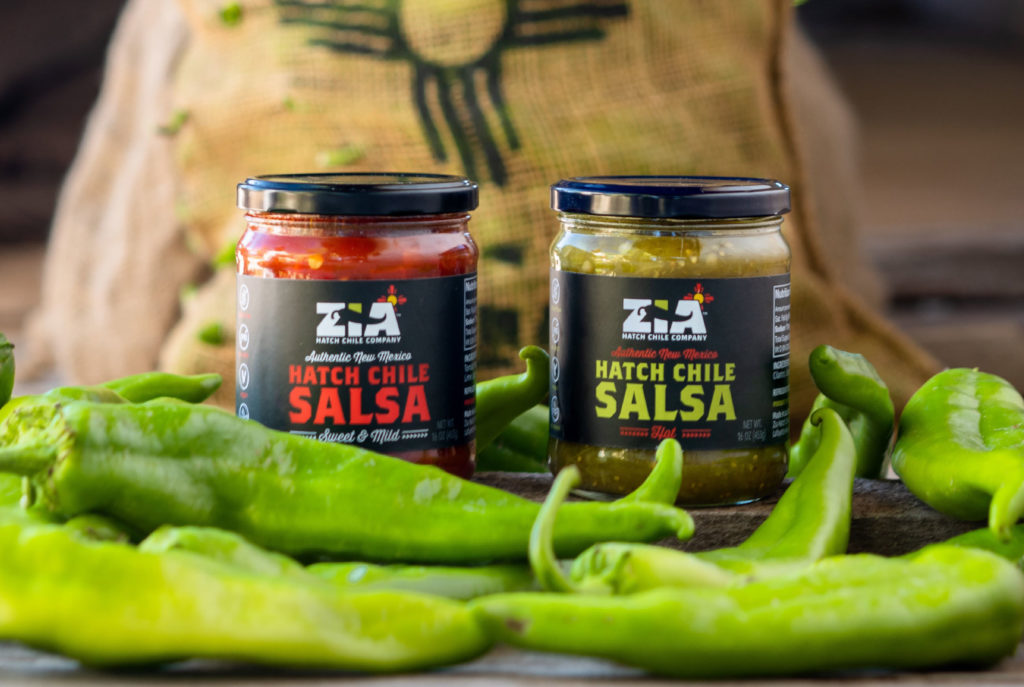Two jars of Zia Hatch Chile Salsa behind several green peppers
