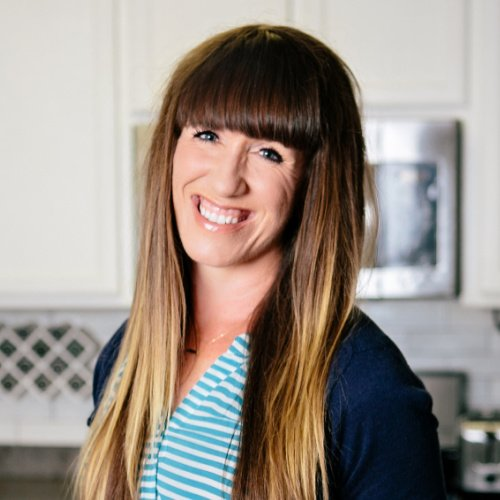 A headshot of Autumn Michaelis smiling, wearing a light blue shirt with a navy blue cardigan. In the background of the shot is a white kitchen