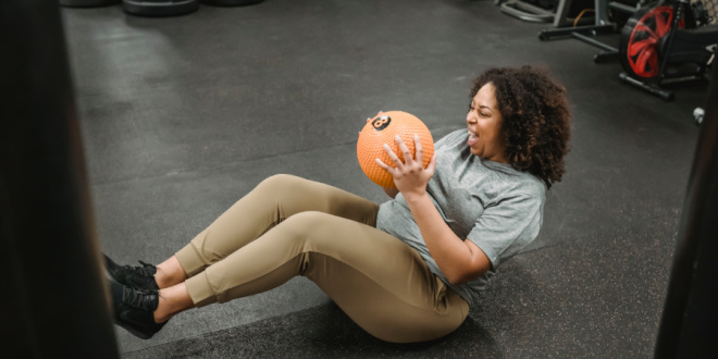 A woman smiles as she holds boat pose with a medicine ball in her hands