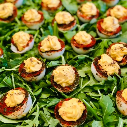 Deviled eggs with herbs and spices on a bed of greens