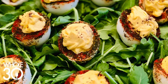 Whole30 deviled eggs on bed of arugula