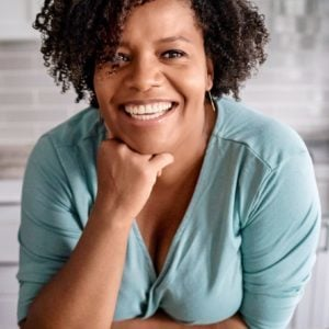Althea Brown in a blue shirt, with her hand on her chin smiling at the camera.
