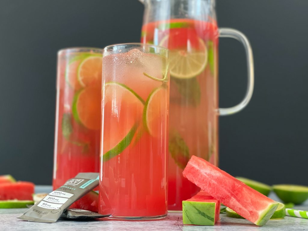 Two glasses and a pitcher of LMNT Watermelon Refresher